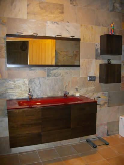 Baño revestido en piedra natural. Mobiliario en madera maciza