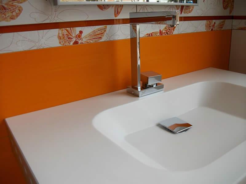 Grifería monomando alto diseño sobre lavabo de Corian